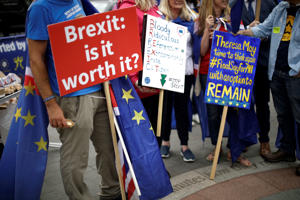 In this photo taken Wednesday, June 20, 2018, anti-Brexit, pro-EU supporters hold placards during a protest near the Houses of Parliament in London. The divisions opened up by the 2016 referendum have not healed, but hardened, splitting Britain into two camps: leavers and remainers. Almost the only thing the two groups share is pessimism about the way Brexit is going. (AP Photo/Matt Dunham)