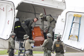 Policemen load coffins -allegedly with the remains of the press team of Ecuadorean newspaper El Comercio- to a plane in Tumaco, Colombia on June 22, 2018, to be transferred to the Legal Medicine offices in Cali for identification. - Colombian authorities have recovered what they believe to be the bodies of a three-man Ecuadoran press team kidnapped and killed on the two countries' border. (Photo by CARLOS AYALA / AFP)        (Photo credit should read CARLOS AYALA/AFP/Getty Images)