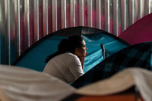 A migrant woman rests at her tent at Juventud 2000 migrant shelter in Tijuana on June 20, 2018. - US President Donald Trump said Wednesday he would sign an executive order to keep migrant families together at the border with Mexico, amid an escalating uproar over the separation of children from their parents. (Photo by GUILLERMO ARIAS / AFP)        (Photo credit should read GUILLERMO ARIAS/AFP/Getty Images)