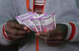 A trader counts new 2,000-rupee notes at a wholesale vegetable market in Bangalore, India, Friday, Dec. 30, 2016. India yanked most of its currency bills from circulation without warning, delivering a jolt to the country's high-performing economy and leaving countless citizens scrambling for cash. Still, as Friday's deadline for depositing old 500- and 1,000-rupee notes draws to a close, Prime Minister Narendra Modi's government has called the demonetization drive a great success in drawing out tax dodgers and eliminating graft.