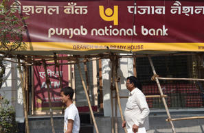 Indian men walk past signage for the state-owned Punjab National Bank (PNB) in Mumbai on February 14, 2018.India's second-largest state-run bank said February 14 it had detected fraud of almost $1.8 billion at one of its branches, sending its shares plunging more than seven percent. The PNB, one of several state-owned lenders the government is trying to clean up, said transactions worth $1.77 billion had been made 'for the benefit of a few select account holders with their apparent connivance'.