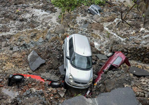 Damaged vehicles are pictured amongst debris after a landslide following heavy monsoon rain showers in Mumbai on June 25
