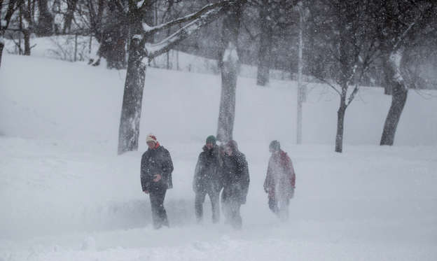 Slide 1 of 35: File images of people during a blizzard.