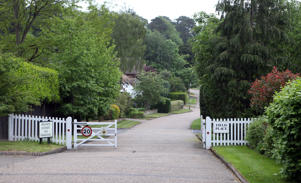 General view of a road leading to Crossfield Place, a private residential street in Weybridge, Surrey
