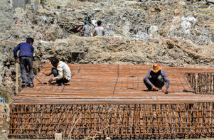 Construction workers processing reinforcing steel in India.
