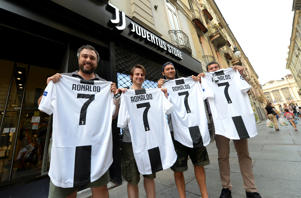 Juventus supporters hold, after buying, the original Juventus' jersey printed with the name and number of Cristiano Ronaldo after his transfer to Juventus in Turin, Italy July 10, 2018.