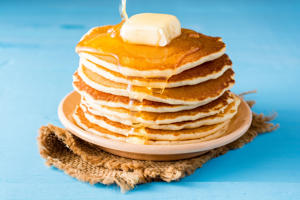 Pancakes with butter and honey on blue wooden table