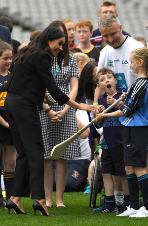 Prince Harry and Meghan, the Duchess of Sussex, meet some of the participants after watching a demonstration of traditional Gaelic sports at Croke Park in Dublin, Ireland, July 11, 2018. REUTERS/Cathal McNaughton