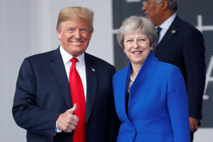 U.S. President Donald Trump gives a thumbs up while he and Britain's Prime Minister Theresa May take part in a family photo at the start of the NATO summit in Brussels, Belgium July 11, 2018.   REUTERS/Kevin Lamarque