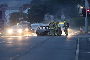 Firefighters deal with a burnt out car in the Cherryhill area of Dundonald in east Belfast.