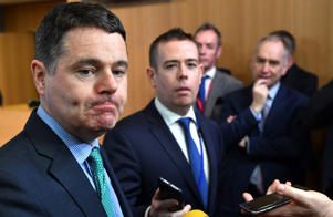 Irish Finance Minister Paschal Donohoe, left, speaks with the media prior to a meeting of the eurogroup at the EU Council building in Brussels on Monday, Feb. 19, 2018. Ireland is withdrawing its candidate, Philip Lane, for European Central Bank vice president, making it almost certain that Spain's finance minister, Luis de Guindos, will get the job. (AP Photo/Geert Vanden Wijngaert)