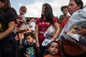 a group of people standing next to a child: Migrants from Central America arriving at the bus station in McAllen, Tex., after being released from government detention in June.