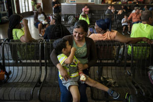 a group of people standing next to a fence: Mirce Alva Lopez, 31, with her 3-year-old son, Adan, at the bus station in Phoenix this week after being reunited.
