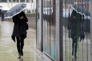 File photo: A pedestrian shelters from the rain in London