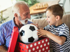 Grandfather presenting gift to happy grandson