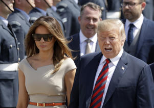 U.S. President Donald Trump and First Lady Melania Trump are greeted after disembarking from Air Force One as they arrive at London Stansted Airport in Stansted, England, Thursday, July 12, 2018. Trump is making his first trip to Britain as president after a tense summit with NATO leaders in Brussels and on the heels of ruptures in British Prime Minister Theresa May's government because of the crisis over Britain's exit from the European Union.