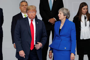 U.S. President Donald Trump and Britain's Prime Minister Theresa May talk as NATO leaders pose for a family photo at the start of the NATO summit in Brussels, Belgium July 11, 2018.   REUTERS/Yves Herman