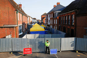 A police officer stands in front of screening erected behind John Baker House as forensic tents are erected, after it was confirmed that two people had been poisoned with the nerve-agent Novichok, in Amesbury, Britain, July 5, 2018. REUTERS/Henry Nicholls