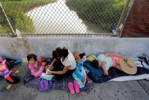 Immigrants from Cuba and Guatemala seeking asylum in the United States wait on the Matamoros International Bridge above the Rio Grande, Friday, June 29, 2018, in Matamoros, Mexico. (AP Photo/Eric Gay, File)