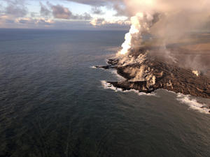 This photo provided by the U.S. Geological Survey shows where lava from Kilauea Volcano is entering the ocean and the resulting laze plume where lava is entering the sea at Kapoho on the island of Hawaii at dawn Wednesday, June 13, 2018. As of June 12, lava entering the ocean had added about 100 hectares (250 acres) of new land to the Island of Hawaii.USGS image taken. (U.S. Geological Survey via AP)