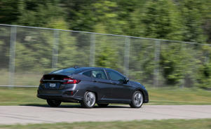 a person riding on the back of a car going down the road: Honda Clarity Plug-In Hybrid Tested: Honda's Sci-Fi Future
