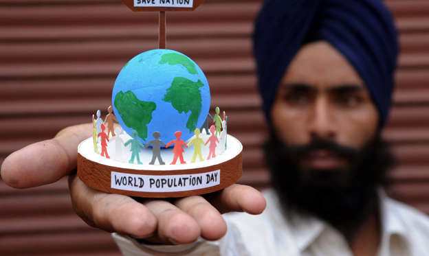 Slide 1 of 13: Indian artist Gurpreet Singh poses with a handmade globe and silhouettes of residents in Amritsar on July 10, 2012, on the eve of World Population Day. AFP PHOTO /NARINDER NANU (Photo credit should read NARINDER NANU/AFP/GettyImages)