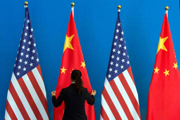A Chinese woman adjusts the Chinese national flag near U.S. national flags before a Strategic Dialogue expanded meeting that's part of the U.S.-China Strategic and Economic Dialogue at the Diaoyutai State Guesthouse in Beijing.