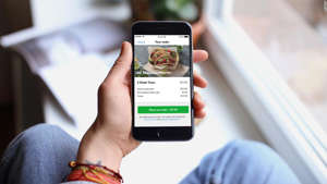 a hand holding a cellphone: If you're ordering regularly via Grubhub, you can get up to $120 in annual dining credits with the Amex Gold card.