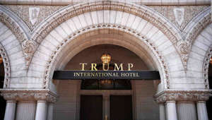 a large clock mounted to the side of a building: WASHINGTON, DC - AUGUST 10: The Trump International Hotel is shown on August 10, 2017 in Washington, DC. The hotel, located blocks from the White House, has become both a tourist attraction in the nation's capital and also a symbol of President Trump's intermingling of business and politics. (Photo by Win McNamee/Getty Images)