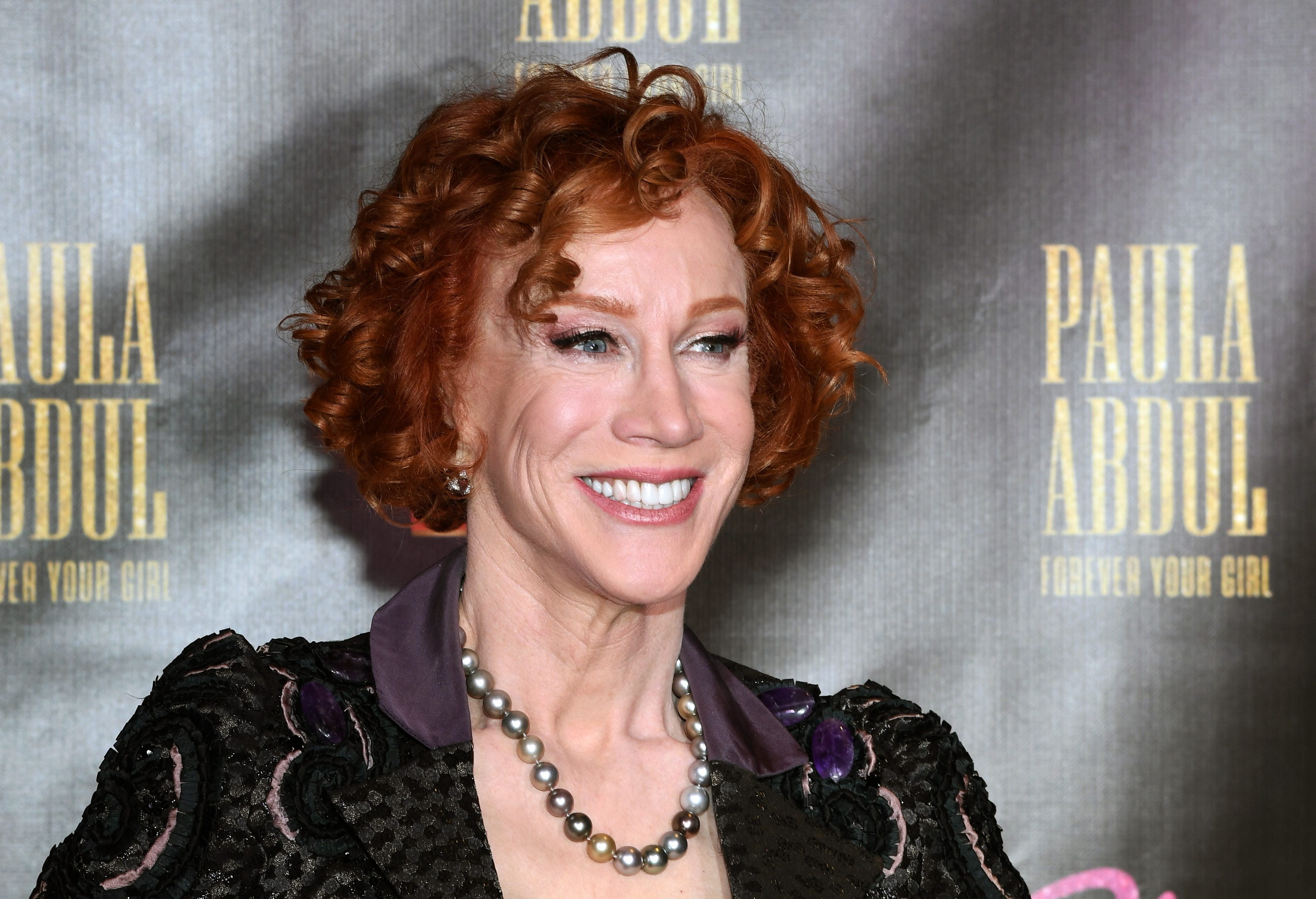 Kathy Griffin wearing a purple shirt and smiling at the camera Kathy Griffin attends the official opening of Paula Abdul's Flamingo Las Vegas residency