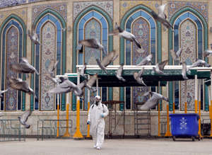 A worker in a protective suit sprays disinfectants near Imam Abbas shrine as a precaution against the coronavirus, following the outbreak, in the holy city of Kerbala, Iraq March 15, 2020.REUTERS/Abdullah Dhiaa Al-deen     TPX IMAGES OF THE DAY