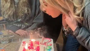 a woman sitting at a table with a birthday cake
