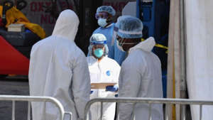 a group of people in a room: US records 2,300 COVID-19 deaths as pandemic rises with holidays