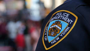 a close up of a person wearing a costume: NYPD officers wear mourning bands for those lost to COVID-19