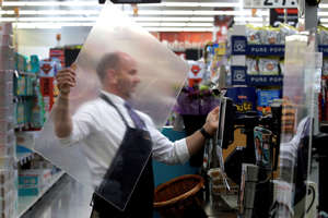 FILE - In this March 26, 2020, file photo, Dave Herrick installs a plexiglass panel at a checkout lane at a Hy-Vee grocery store in Overland Park, Kan. Grocery workers across the globe are working the front lines during lockdowns meant to keep the coronavirus from spreading.