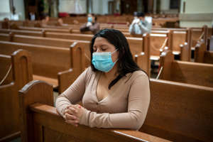 a woman sitting on a chair: Monica Asitimbay prays at Holy Trinity Church in Hackensack, New Jersey, on Sunday, May 17, 2020, the first the day the church reopened during the coronavirus pandemic.