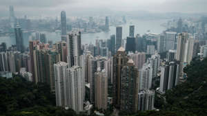 a view of Victoria Peak with tall buildings in the background: Hong Kong offering payments to residents who test positive for COVID-19 amid rise in cases