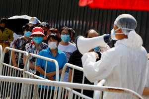 People line up to receive nucleic acid tests at a temporary testing site after a new outbreak of the coronavirus disease (COVID-19) in Beijing, China June 30, 2020.  REUTERS/Thomas Peter     TPX IMAGES OF THE DAY