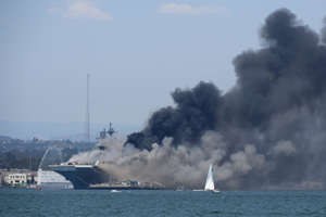 a small boat in a body of water with smoke coming out of it: Smoke rises from the USS Bonhomme Richard at Naval Base San Diego Sunday, July 12, 2020, in San Diego after an explosion and fire Sunday on board the ship at Naval Base San Diego.