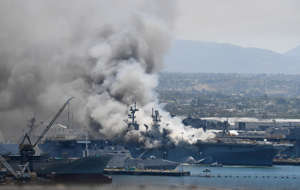 a large ship in a body of water with smoke coming out of it: Smoke rises from the USS Bonhomme Richard at Naval Base San Diego in July.