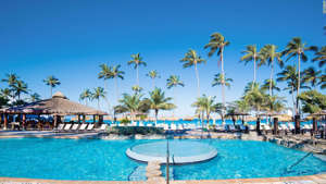 a row of palm trees next to a swimming pool: The Holiday Inn Resort Aruba-Beach.