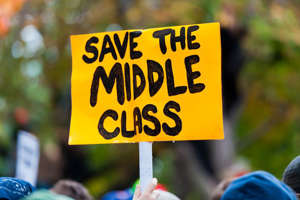 a person holding a sign: Middle class can mean different things to different people. You can think of middle class as a certain lifestyle, a state of mind, or a strict measurement of wealth. And how you define middle class determines who falls into it.Using annual incomes and the cost of living around the country as barometers, the experts at the Pew Research Center have concluded that 52% of Americans qualify as middle class—but that portion can vary widely depending where you live. According to a Pew study released last fall, the median income of middle-class American households is $74,015, based on Census data from 2016, the latest available. (Pew defines middle class as two-thirds to twice the U.S. median household income, adjusted for household size.)As you can see in the map below, that benchmark income tops $84,000 in Rhode Island and Maryland and approaches $75,000 in Florida.So where do all these middle-class folks live? Pew drilled down by community as well, and found that the 10 highest concentrations of middle-class Americans reside in the Midwest and Northeast. In Sheboygan, Wisc., the middle class makes up about 65% of the population. In Laredo, Texas, on the other hand, only 39% percent of residents qualify.