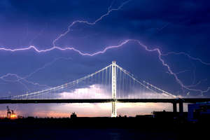 a view of a large body of water: Lightning forks over the San Francisco-Oakland Bay Bridge as a storm passes over Oakland, Calif., Sunday, Aug. 16, 2020. Numerous lightning strikes early Sunday sparked brush fires throughout the region.