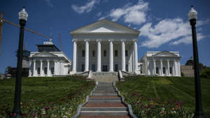 a clock tower in front of a house with Virginia State Capitol in the background: Virginia lawmakers vote for segregationist's statue to be removed from Capitol grounds