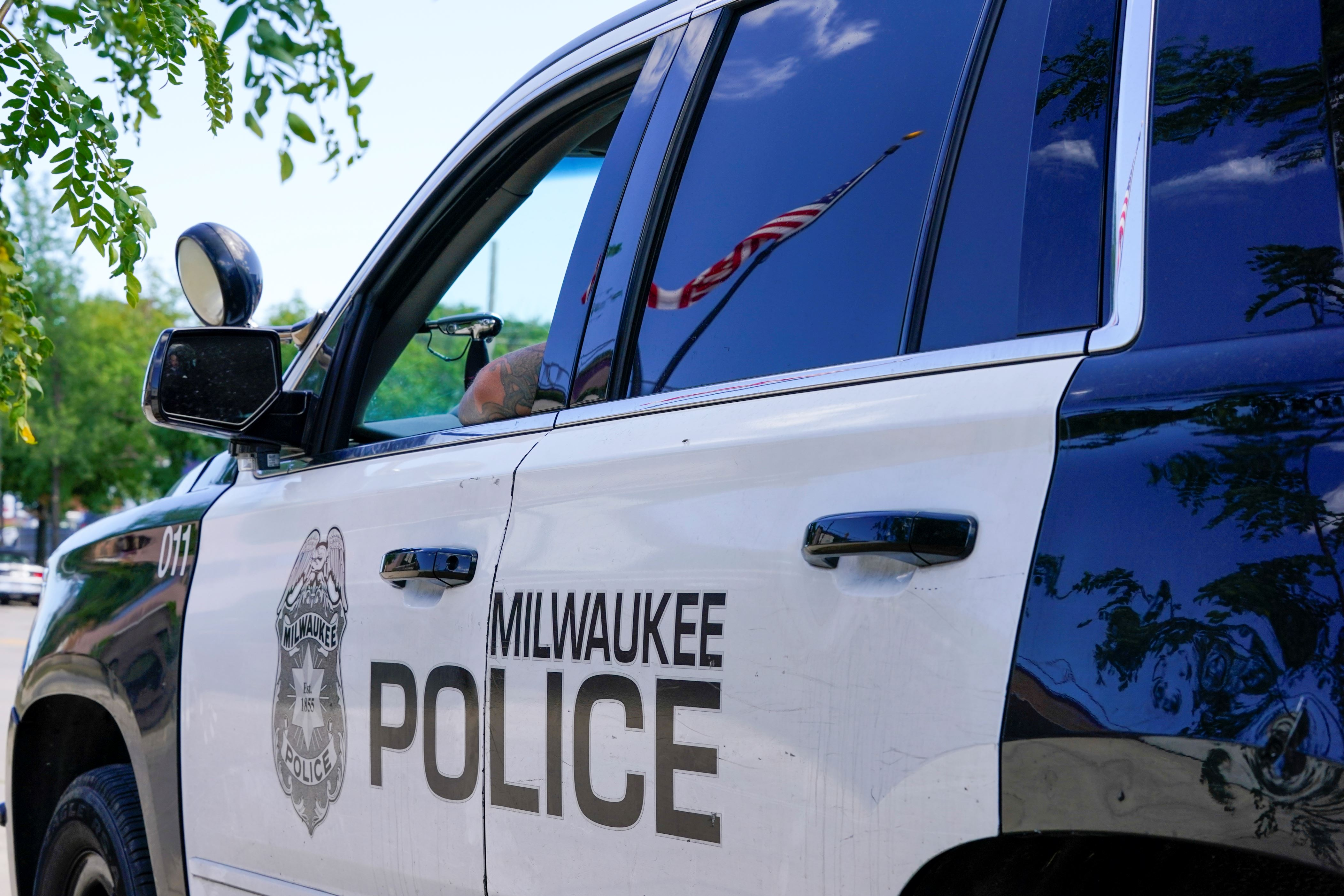A flag is reflected in the window of a Milwaukee Police Department vehicle Tuesday Aug. 18 2020 in Milwaukee
