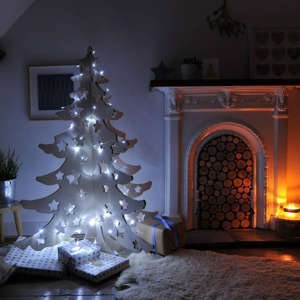 a christmas tree in a room: £345.00Shop NowThis 4ft tree made from birch plywood features charming festive cut-out stars. It looks wonderful once draped with fairy lights.