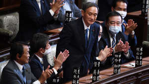 Yoshihide Suga et al. standing next to a person in a suit and tie: Yoshihide Suga is applauded after he was elected as Japan's Prime Minister by the lower house of the Diet in Tokyo on September 16.