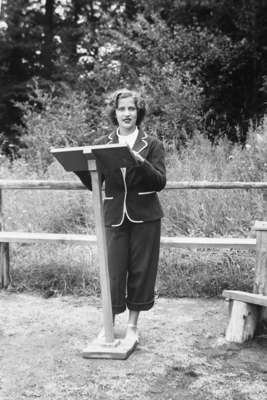 a person sitting on a bench in front of a fence: Ruth Bader, age age 15 in 1948, giving a sermon as the camp rabbi at Che-Na-Wah in Minerva, N.Y.