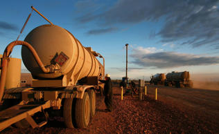 A worker transfers barrels of oil into a tank at a facility outside Alexander, N...