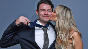 a person posing for the camera:  Lachie Neale of the Lions poses with his wife Julie Neale after winning the Brownlow Medal